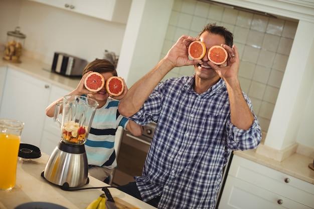 Padre e figlia che coprono gli occhi di arancia rossa