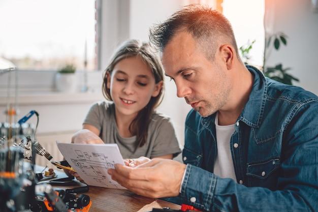 Padre e figlia che esaminano gli schemi elettronici