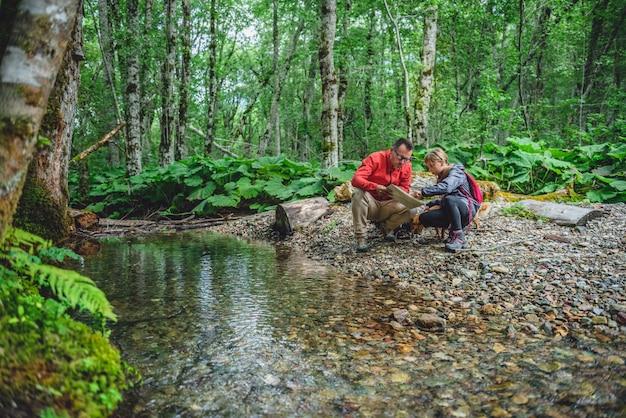 Padre e figlia che fanno un'escursione nella foresta e che controllano mappa