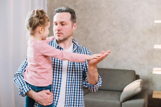 Padre e figlia che giocano gioco d'applauso mentre se lo esaminano