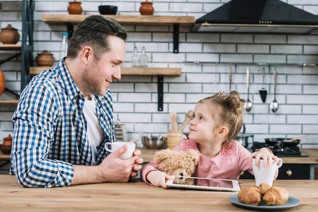 Padre e figlia che se lo esaminano mentre bevono il caffè in cucina