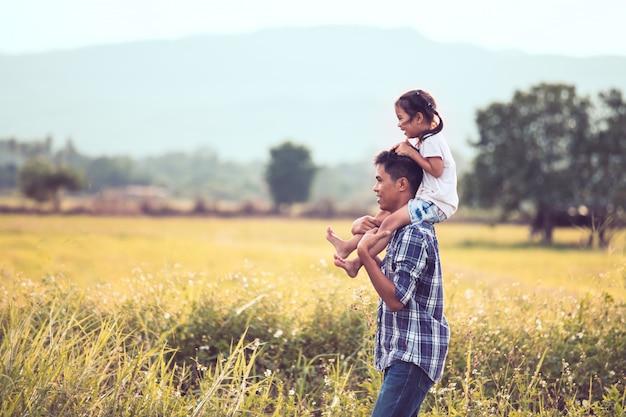 Padre e figlia che si diverte a giocare insieme nel campo di grano