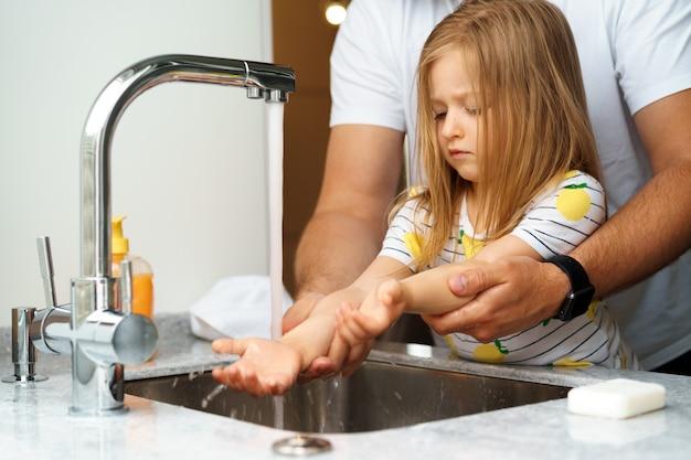 Padre e figlia che si lavano le mani sopra il lavandino in una cucina