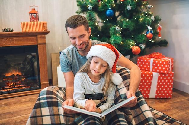 Padre e figlia che si siedono sul pavimento sulla coperta e sul libro di lettura.