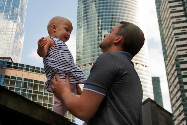 Padre e figlia di un anno contro il cielo e i grattacieli. viaggia con i bambini, lo sviluppo dell'intelligenza emotiva.