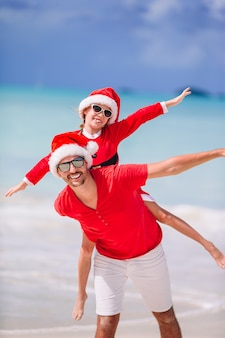 Padre e figlia in santa hat si divertono in spiaggia tropicale