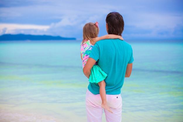 Padre e figlia piccola, guardando il mare in spiaggia tropicale