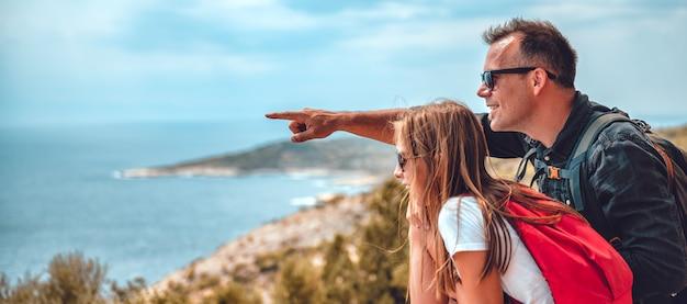 Padre e figlia seduti sul bordo della scogliera sul mare