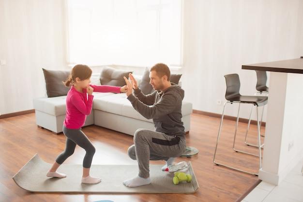 Padre e figlia si allenano a casa. allenamento nell'appartamento. fai sport a casa. il padre insegna a mantenere un pugno. pugilato insieme. allenamento di boxe a casa