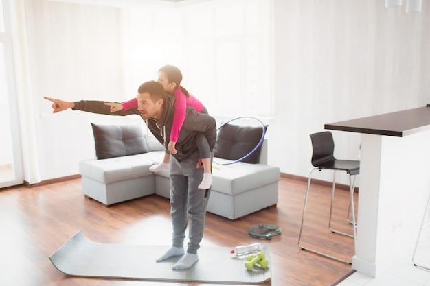 Padre e figlia si allenano a casa. allenamento nell'appartamento. fai sport a casa. la figlia le è salita sulla schiena e si diverte.