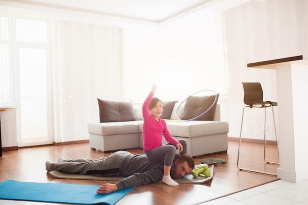 Padre e figlia si allenano a casa. allenamento nell'appartamento. fai sport a casa. papà è molto stanco. la figlia le è salita sulla schiena e si diverte.