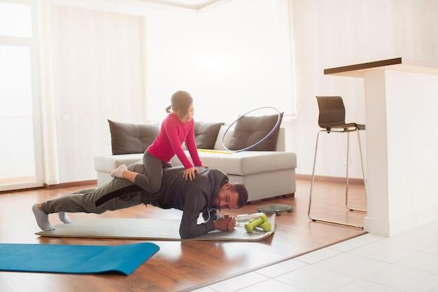 Padre e figlia si allenano a casa. allenamento nell'appartamento. sport in condizioni di casa. fanno la tavola facendo. la figlia è salita sul papà. si sta alzando da terra.