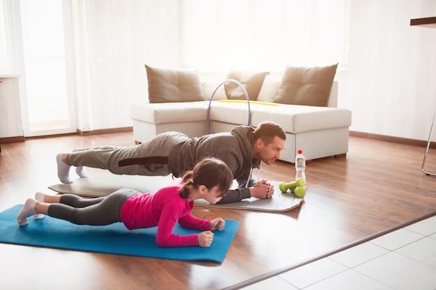 Padre e figlia si allenano a casa. allenamento nell'appartamento. sport in condizioni di casa. fanno la tavola facendo.