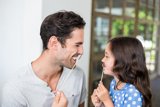 Padre e figlia sorridenti con i baffi artificiali