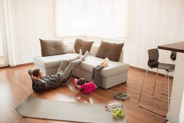 Padre e figlia stanno allenando addominali a casa. allenamento nell'appartamento.