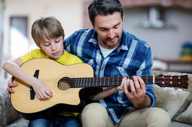 Padre e figlio a suonare una chitarra