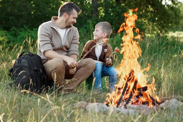 Padre e figlio accanto al fuoco sulla natura verde.