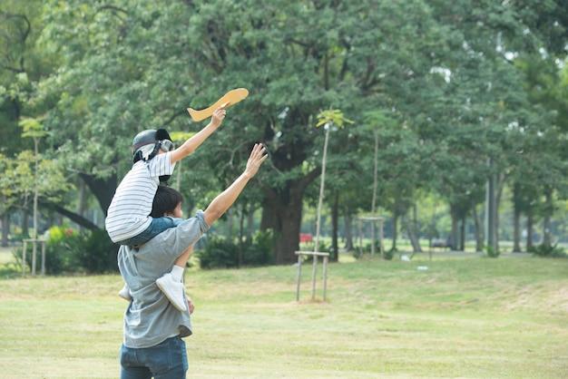 Padre e figlio asiatici giocano con l'aereo di carta nel parco pubblico in estate, la paternità e il bambino hanno attività ricreative insieme.