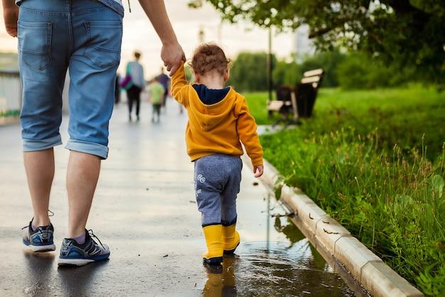 Padre e figlio che camminano all'aria aperta in stivali di gomma sulle pozzanghere dopo la pioggia in giornata estiva.