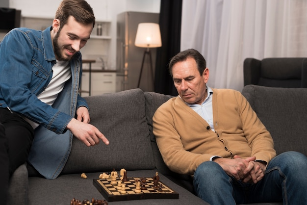 Padre e figlio che giocano a scacchi in salotto