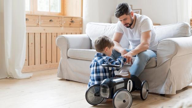 Padre e figlio che giocano con la macchina da corsa