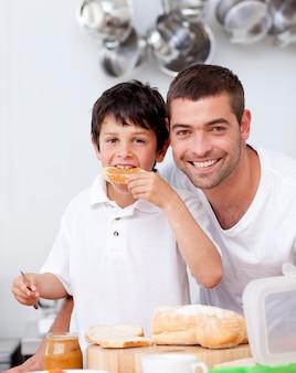 Padre e figlio che mangiano un pane tostato
