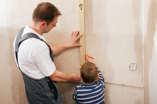 Padre e figlio che misurano muro a secco