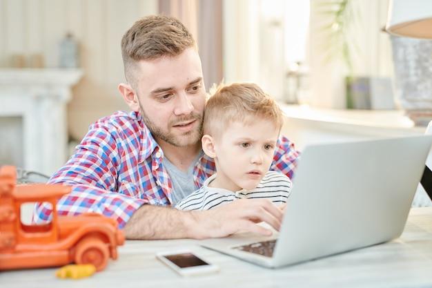Padre e figlio che per mezzo del computer portatile