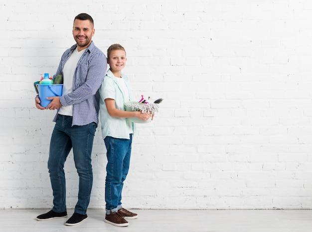 Padre e figlio che posano con i prodotti per la pulizia e lo spazio della copia