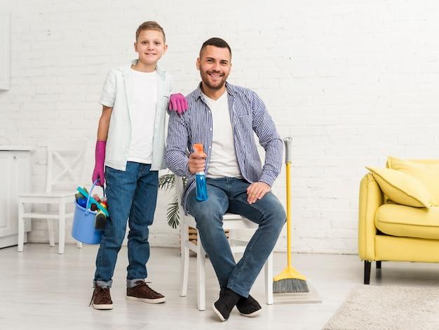 Padre e figlio che posano mentre pulendo la casa