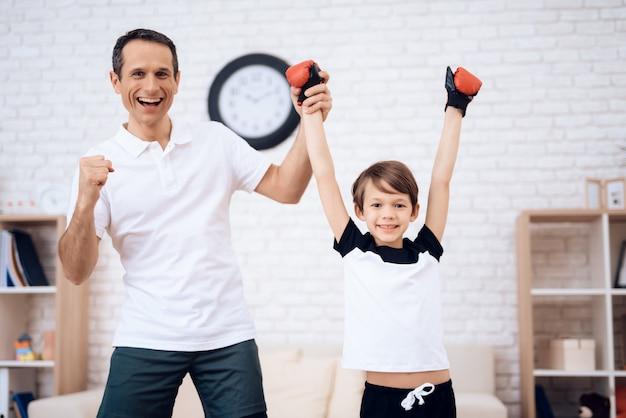 Padre e figlio che posano sulla macchina fotografica in guantoni da pugile.