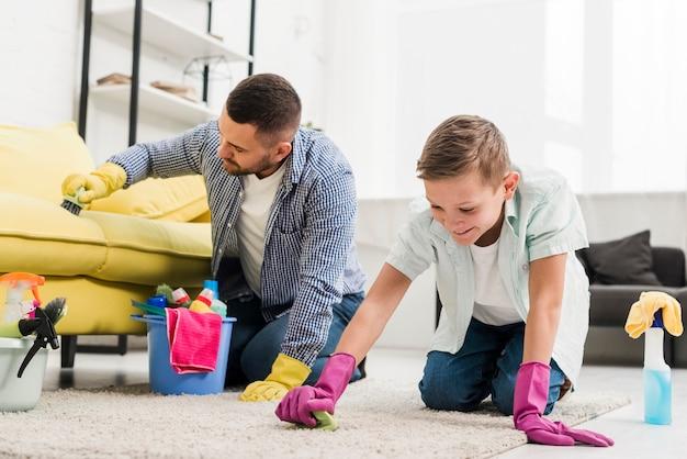 Padre e figlio che puliscono il tappeto
