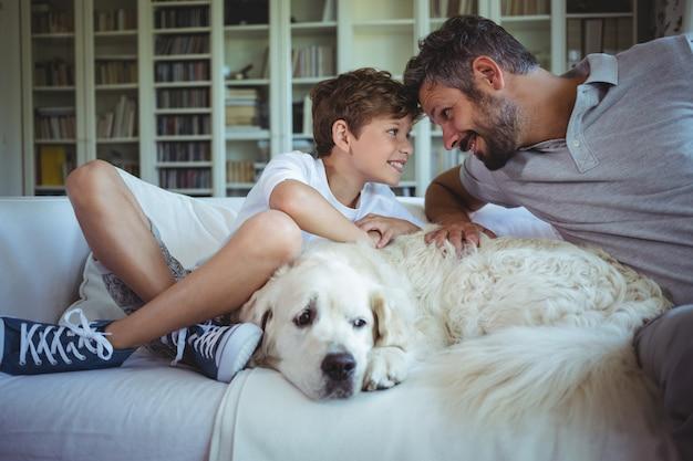 Padre e figlio che si siedono sul sofà con il cane di animale domestico in salone
