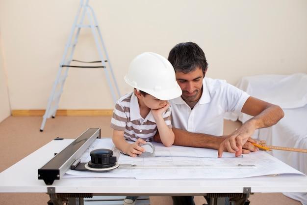 Padre e figlio che studiano lavorando con i piani