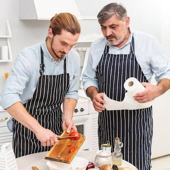 Padre e figlio che tagliano i pomodori