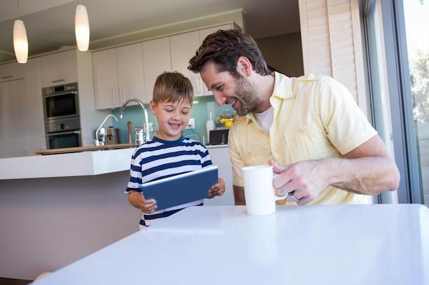 Padre e figlio che utilizza il pc della compressa nel salone a casa