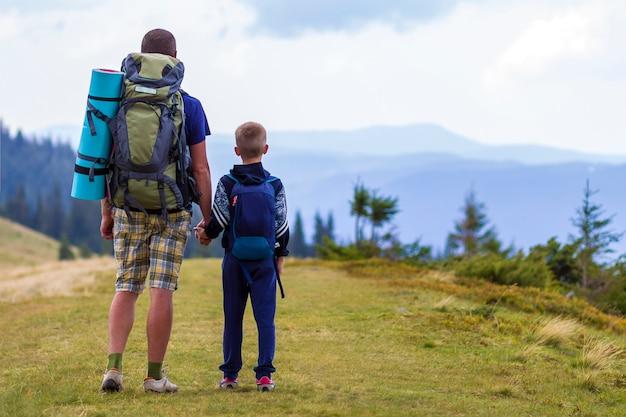 Padre e figlio con gli zaini che fanno un'escursione insieme