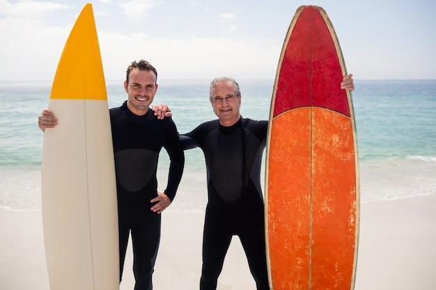 Padre e figlio con la tavola da surf che sta sulla spiaggia