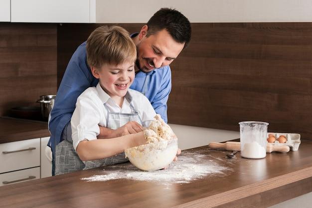 Padre e figlio dell'angolo alto che producono insieme pasta