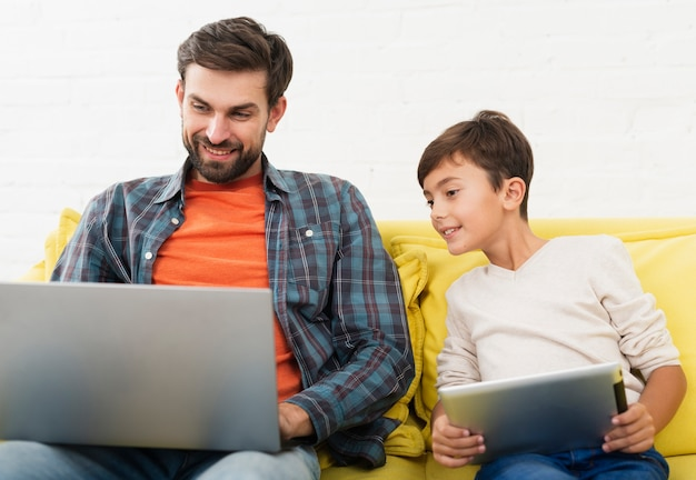 Padre e figlio di vista frontale che osservano sul computer portatile