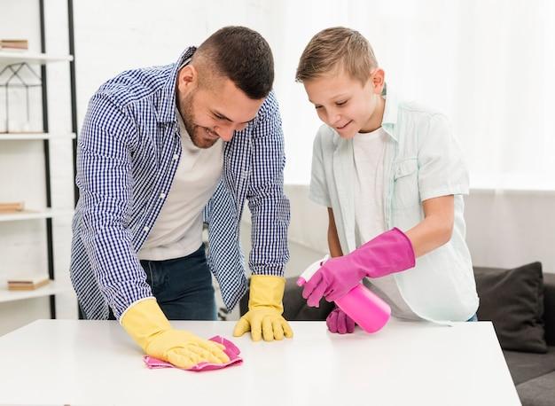 Padre e figlio felici che godono della pulizia