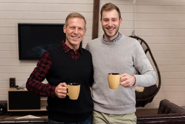 Padre e figlio felici che posano tenendo le tazze