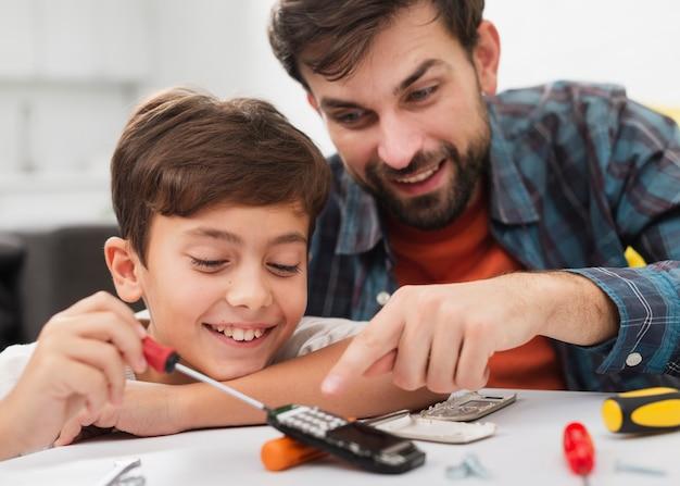 Padre e figlio felici che riparano un telefono