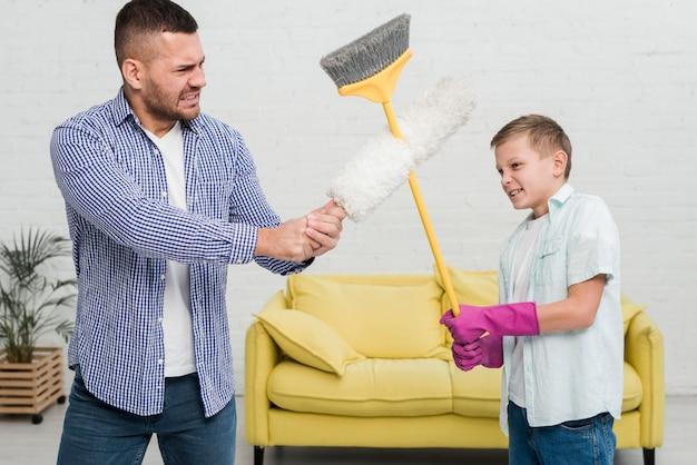 Padre e figlio giocano a combattere con la scopa e lo spolverino