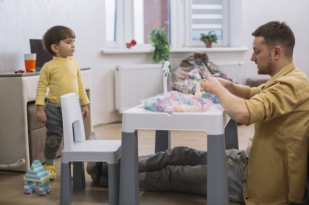 Padre e figlio giocano con i pezzi lego