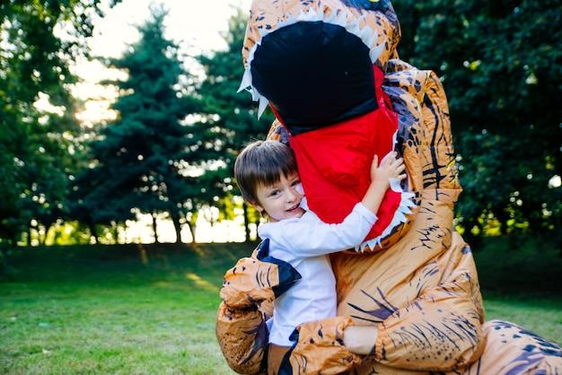 Padre e figlio giocano nel parco, con un costume da dinosauro, divertendosi con la famiglia all'aperto