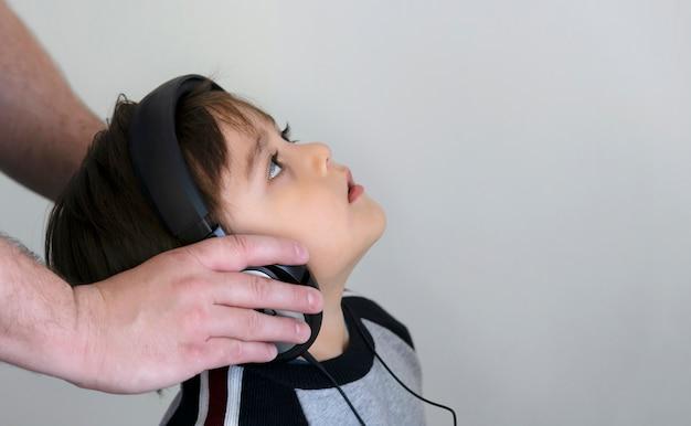 Padre e figlio in cuffia ascoltano musica