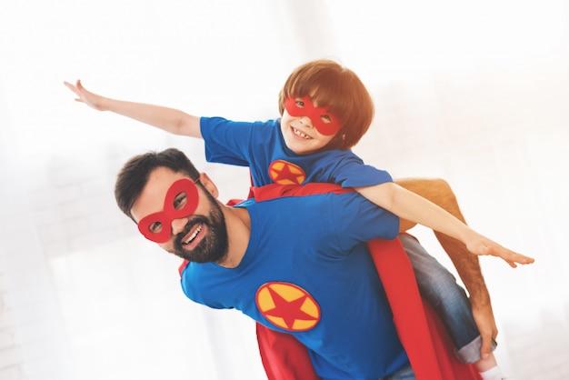 Padre e figlio indossano maschere da supereroi.