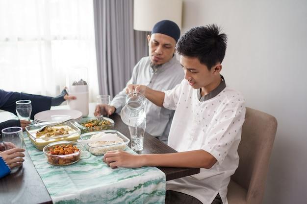 Padre e figlio musulmani che mangiano insieme una cena