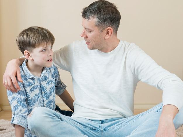 Padre e figlio parlando sul pavimento